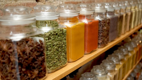 Colorful glass spice jars on a wooden shelf