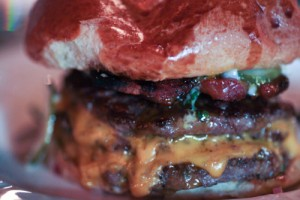 Close up of a double cheese burger with pickle, tomato spilling out