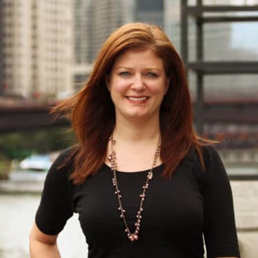Headshot for Jessica S. Red Haired Woman in Black Dress Standing in front of faded Chicago Skyline