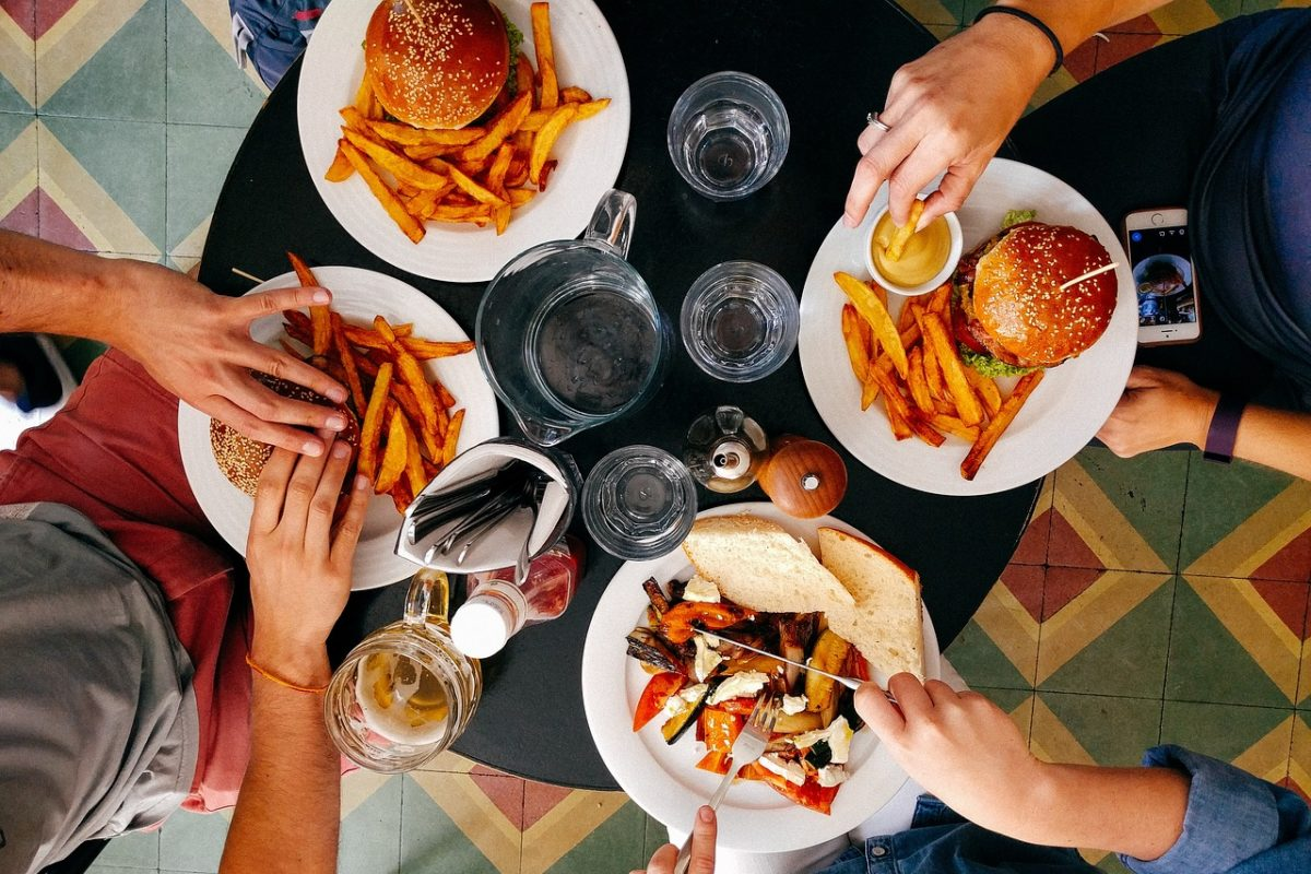 Looking down at a table you see hands and hamburgers with four settings at a table.