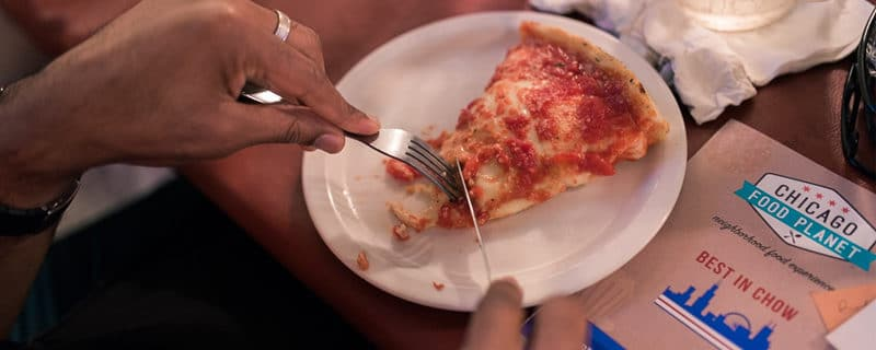 A person's hands cutting a slice of cheese deep dish pizza from Lou Malnati's with a Best In Chow booklet next to the plate.
