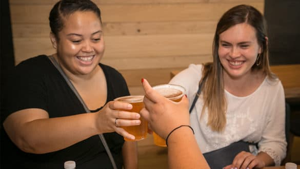 Women Smiling and Cheers Beers at Tiny Tavern